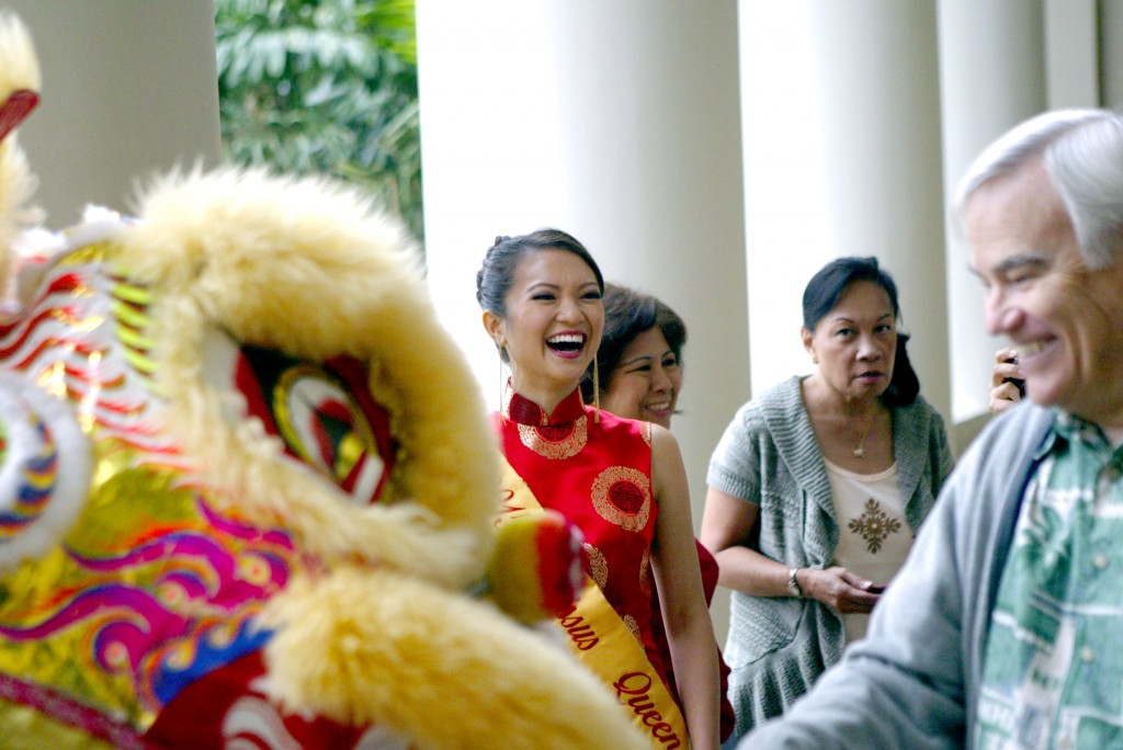 2015 Narcissus Queen and University of Hawai'i civil engineering student—Erica Wong—enjoys UH Mānoa Chancellor Robert Veley-Roman's attempt at a tribute during a traditional Chinese Lion Dance at Hawai'i Hall, marking the arrival of the Chinese New Year at UH Mānoa.