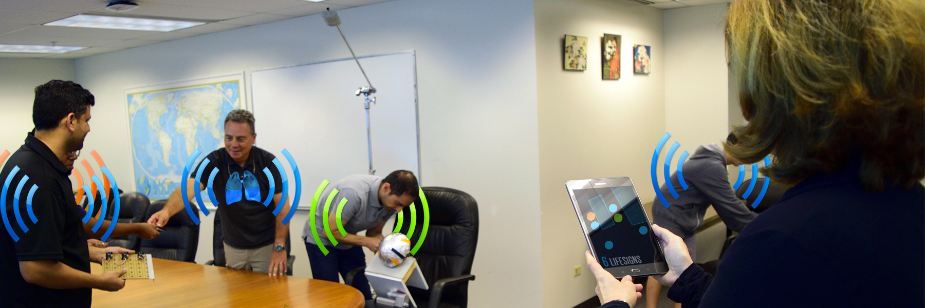 Engineers Work While A Tablet In The Foreground Indicates Six Life-signs Present.