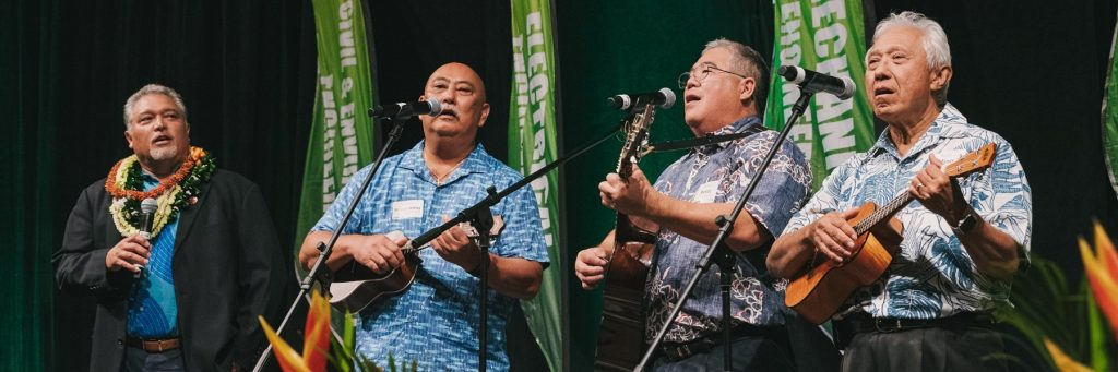 A group of engineers holding musical instruments, singing Hawai'i Aloha.