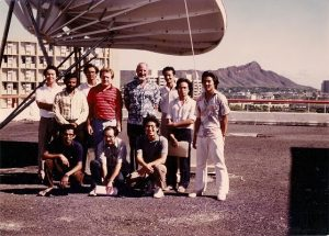 Students standing next to a satellite dish.
