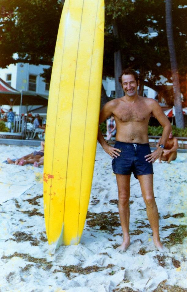Norman Abramson Posing Next To A Surfboard