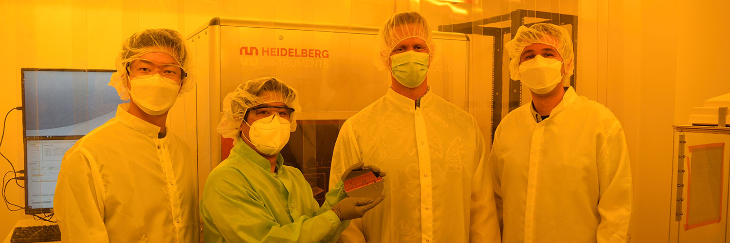 Group Photo Of Researchers Standing In Front Of Microfabrication Machine